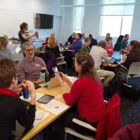 A classroom with faculty grouped around tables, sharing ideas.